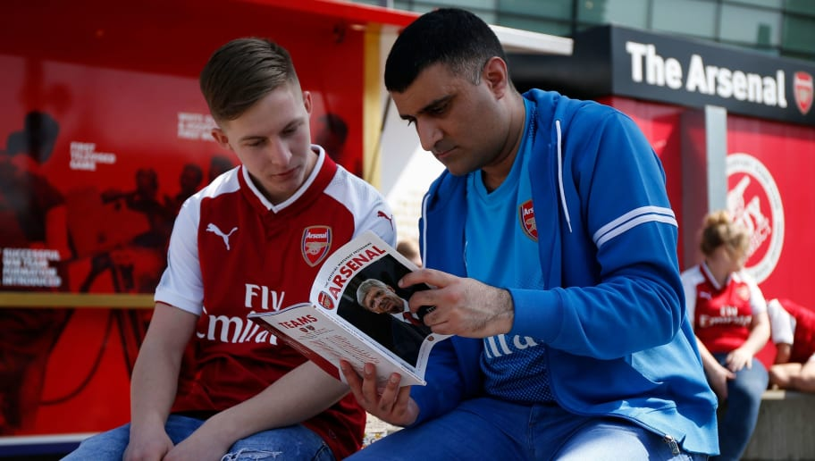 Fans read a match-day programme with a picture on Arsenal's French manager Arsene Wenger on the front during the English Premier League football match between Arsenal and West Ham United at the Emirates Stadium in London on April 22, 2018. (Photo by Ian KINGTON / AFP) / RESTRICTED TO EDITORIAL USE. No use with unauthorized audio, video, data, fixture lists, club/league logos or 'live' services. Online in-match use limited to 75 images, no video emulation. No use in betting, games or single club/league/player publications. /         (Photo credit should read IAN KINGTON/AFP/Getty Images)