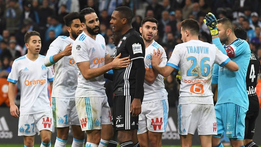 TOPSHOT - Marseille and Lyon footballers argue at the end of the French L1 football match between Marseille and Lyon at The Velodrome Stadium in Marseille, southern France on March 18, 2018. Clashes erupted between players Marseille and Lyon on their return to the locker room, creating confusion for several minutes, after the victory of Lyon 3-2, after a competitive match at the Vélodrome,  on the thirtieth day of France's Ligue 1. / AFP PHOTO / ANNE-CHRISTINE POUJOULAT        (Photo credit should read ANNE-CHRISTINE POUJOULAT/AFP/Getty Images)