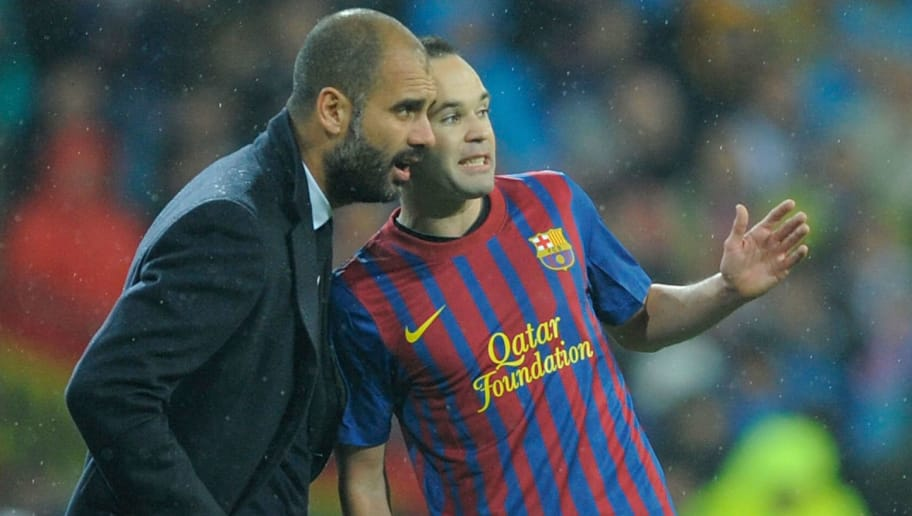 MADRID, SPAIN - DECEMBER 10:  Barcelona head coach Josep Guardiola (L) confers with Andres Iniesta during the La Liga match between Real Madrid and Barcelona at Estadio Santiago Bernabeu on December 10, 2011 in Madrid, Spain.  (Photo by Denis Doyle/Getty Images)