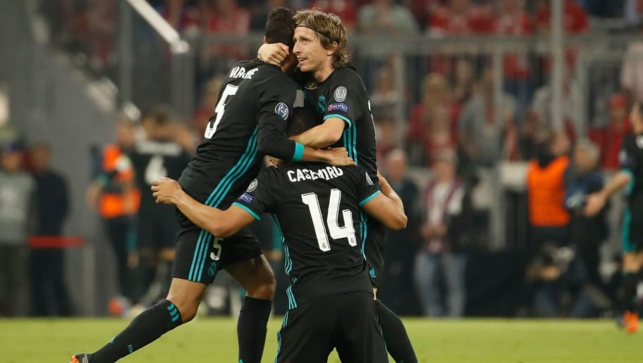 Real Madrid's Brazilian midfielder Casemiro (C), Real Madrid's French defender Raphael Varane (L) and Real Madrid's Croatian midfielder Luka Modric celebrate the 1-2 goal during the UEFA Champions League semi-final first-leg football match FC Bayern Munich v Real Madrid CF in Munich, southern Germany on April 25, 2018. (Photo by Odd ANDERSEN / AFP)        (Photo credit should read ODD ANDERSEN/AFP/Getty Images)