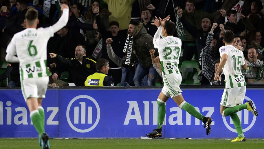 Real Betis' Algerian defender Aissa Mandi (C) celebrates after scoring a goal during the Spanish league football match Real Betis vs Real Madrid at the Benito Villamarin stadium in Sevilla on February 18, 2018. / AFP PHOTO / Cristina Quicler        (Photo credit should read CRISTINA QUICLER/AFP/Getty Images)