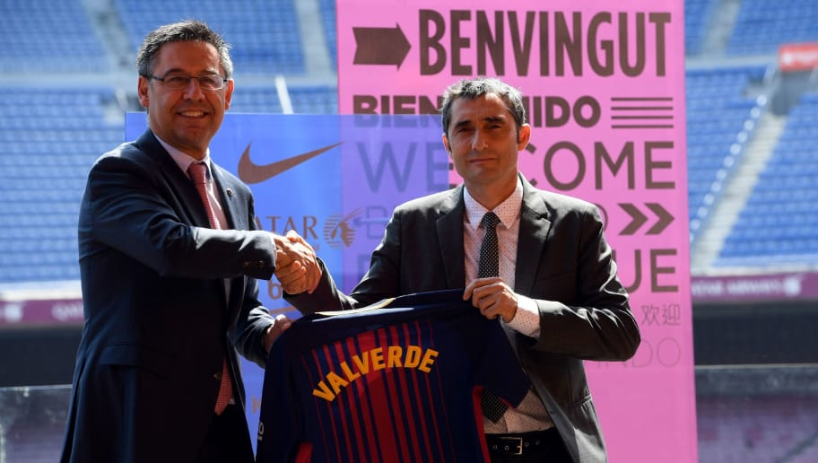 Barcelona's new coach Ernesto Valverde (R) shakes hands with Barcelona's president Josep Maria Bartomeu (L) as they hold a jersey with Valverde's name on it during his official presentation at the Camp Nou stadium in Barcelona on June 1, 2017, after signing his new contract with the Catalan club. / AFP PHOTO / LLUIS GENE        (Photo credit should read LLUIS GENE/AFP/Getty Images)