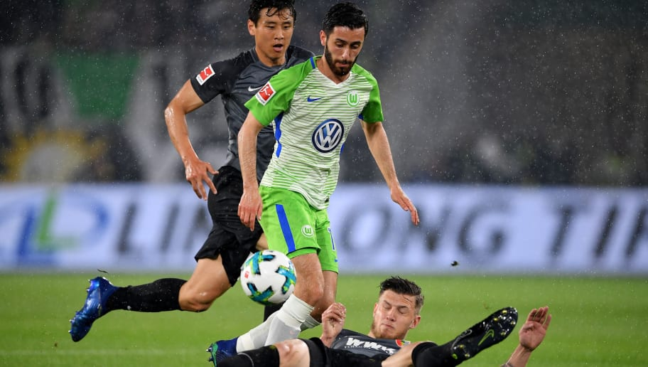 WOLFSBURG, GERMANY - APRIL 13:  Yunus Malli (L) of Wolfsburg and Jeffrey Gouweleeuw of Augsburg battle for the ball during the Bundesliga match between VfL Wolfsburg and FC Augsburg at Volkswagen Arena on April 13, 2018 in Wolfsburg, Germany.  (Photo by Stuart Franklin/Bongarts/Getty Images)