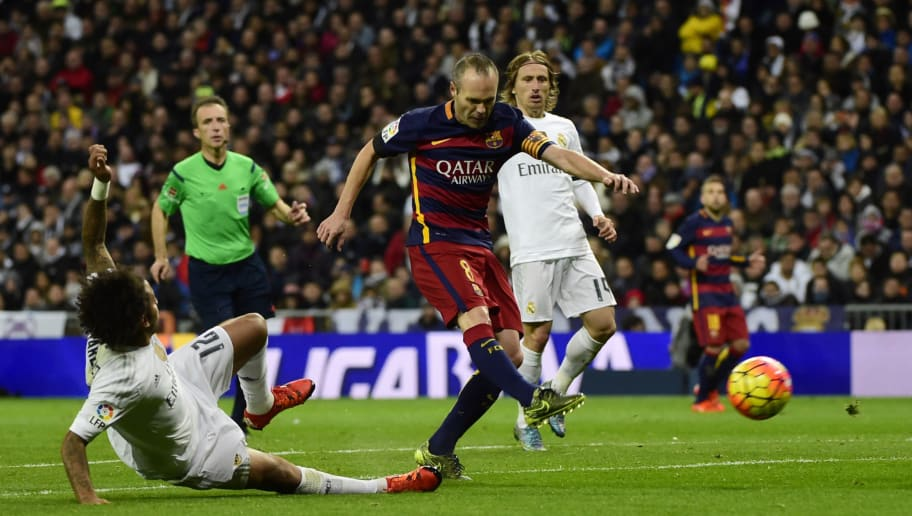 Barcelona's midfielder Andres Iniesta (C) kicks the ball to score during the Spanish league 'Clasico' football match Real Madrid CF vs FC Barcelona at the Santiago Bernabeu stadium in Madrid on November 21, 2015.   AFP PHOTO / PIERRE-PHILIPPE MARCOU / AFP / PIERRE-PHILIPPE MARCOU        (Photo credit should read PIERRE-PHILIPPE MARCOU/AFP/Getty Images)