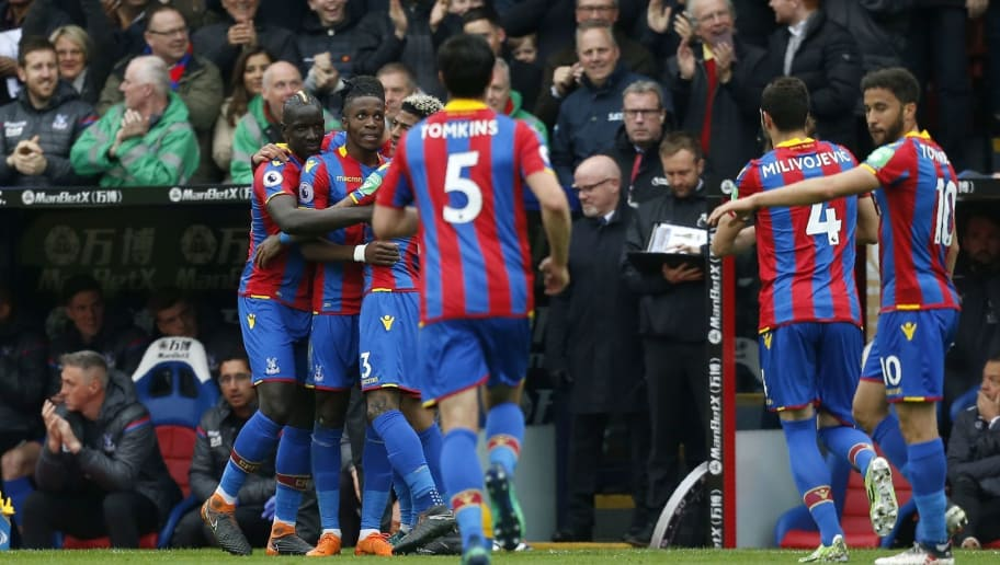 Crystal Palace's Ivorian striker Wilfried Zaha (2L)  celebrates with teammates  after scoring the opening goal during the English Premier League football match between Crystal Palace and Leicester City at Selhurst Park in south London on April 28, 2018. (Photo by Ian KINGTON / AFP) / RESTRICTED TO EDITORIAL USE. No use with unauthorized audio, video, data, fixture lists, club/league logos or 'live' services. Online in-match use limited to 75 images, no video emulation. No use in betting, games or single club/league/player publications. /         (Photo credit should read IAN KINGTON/AFP/Getty Images)