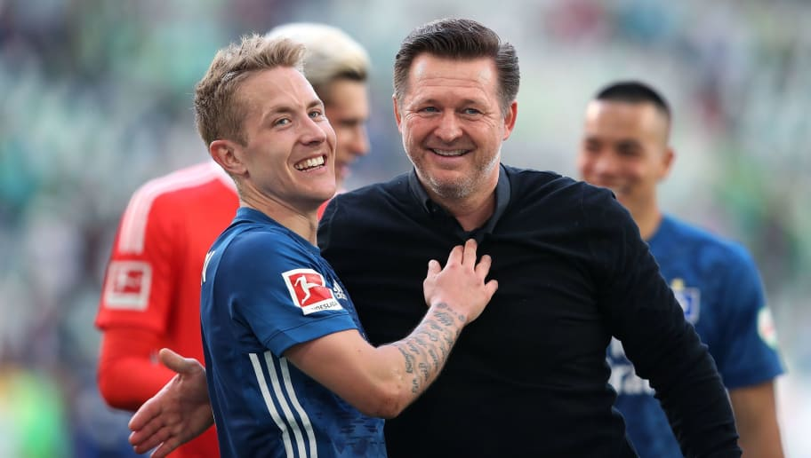 Hamburg's German midfielder Lewis Holtby (L) and Hamburg's German head coach Christian Titz (R) celebrate after the German first division Bundesliga football match VfL Wolfsburg vs Hamburger SV in Wolfsburg, northern Germany, on April 28, 2018. (Photo by Ronny Hartmann / AFP) / RESTRICTIONS: DURING MATCH TIME: DFL RULES TO LIMIT THE ONLINE USAGE TO 15 PICTURES PER MATCH AND FORBID IMAGE SEQUENCES TO SIMULATE VIDEO. == RESTRICTED TO EDITORIAL USE == FOR FURTHER QUERIES PLEASE CONTACT DFL DIRECTLY AT + 49 69 650050        (Photo credit should read RONNY HARTMANN/AFP/Getty Images)