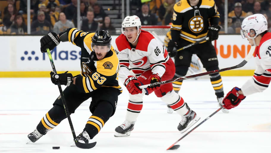 BOSTON, MASSACHUSETTS - MAY 12: Brad Marchand #63 of the Boston Bruins handles the puck against Sebastian Aho #20 of the Carolina Hurricanes during the first period in Game Two of the Eastern Conference Final during the 2019 NHL Stanley Cup Playoffs at TD Garden on May 12, 2019 in Boston, Massachusetts. (Photo by Bruce Bennett/Getty Images)