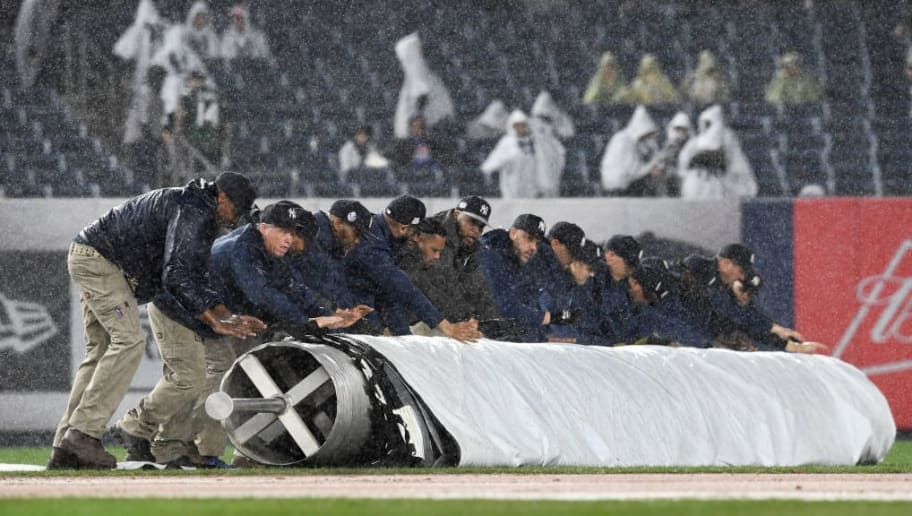 NEW YORK, NEW YORK - APRIL 12: Grounds crew members help put the tarp on the field during a rain delay in the middle of the seventh inning of the game between the Chicago White Sox and the New York Yankees at Yankee Stadium on April 12, 2019 in the Bronx borough of New York City. (Photo by Sarah Stier/Getty Images)