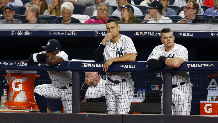 NEW YORK, NEW YORK - OCTOBER 09:  Andrew McCutchen #26, Giancarlo Stanton #27 and Luke Voit #45 of the New York Yankees looks on from the dugout against the Boston Red Sox in Game Four of the American League Division Series at Yankee Stadium on October 09, 2018 in the Bronx borough of New York City. (Photo by Mike Stobe/Getty Images)