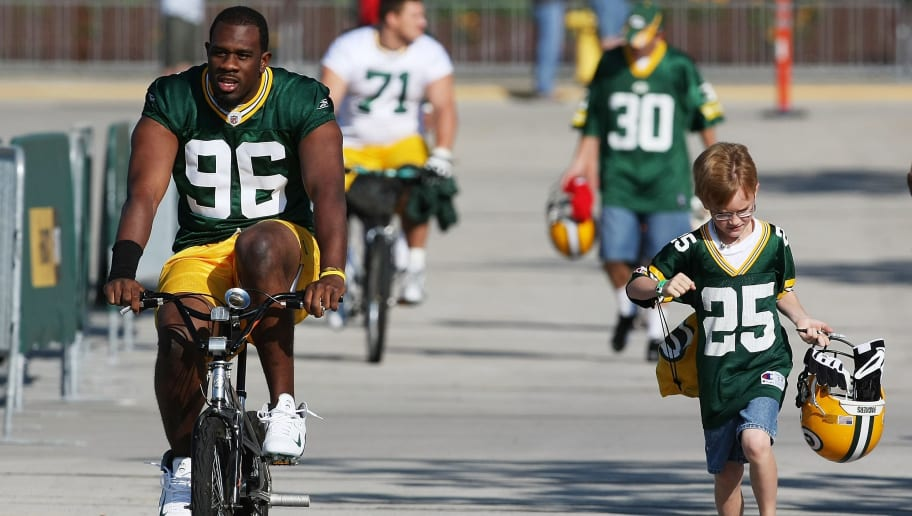 GREEN BAY, WI - JULY 28: Michael Montgomery #96 of the Green Bay Packers rides a bicycle to practice as a young fan carries his helmet during summer training camp on July 28, 2008 at the Hutson Center in Green Bay, Wisconsin. (Photo by Jonathan Daniel/Getty Images)