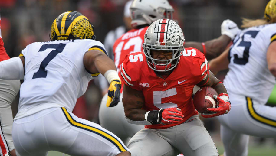 COLUMBUS, OH - NOVEMBER 24:  Mike Weber #5 of the Ohio State Buckeyes looks for room to run in the second quarter as Khaleke Hudson #7 of the Michigan Wolverines closes in at Ohio Stadium on November 24, 2018 in Columbus, Ohio. Ohio State defeated Michigan 62-39.  (Photo by Jamie Sabau/Getty Images)