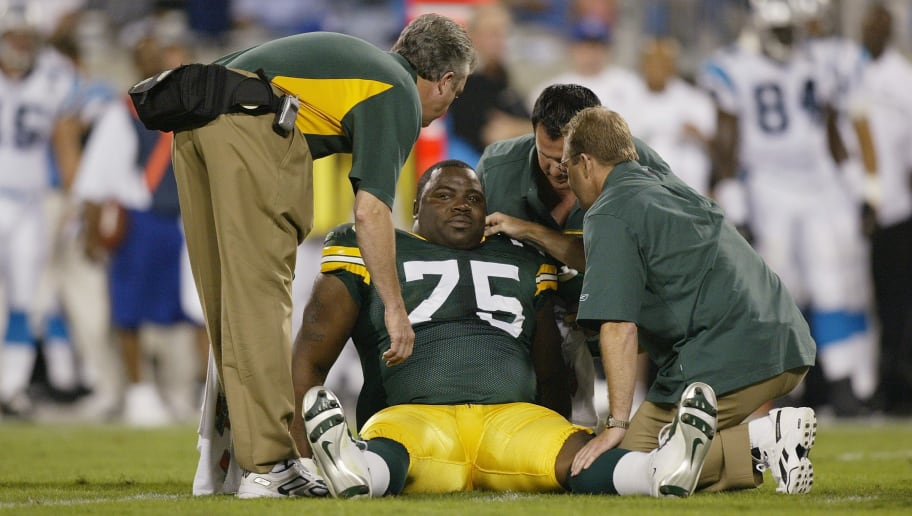 CHARLOTTE, NC - SEPTEMBER 13:  Head trainer Pepper Burruss (L) and two other medical staff of the Green Bay Packer assist injured Packer defensive tackle Grady Jackson #75 during the game against the Carolina Panthers at Bank of America Stadium on September 13, 2004 in Charlotte, North Carolina.  The Packers won 24-14. (Photo by Streeter Lecka/Getty Images)