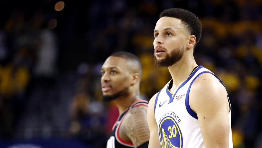 OAKLAND, CALIFORNIA - MAY 14: Damian Lillard #0 of the Portland Trail Blazers and Stephen Curry #30 of the Golden State Warriors look on during the second half in game one of the NBA Western Conference Finals at ORACLE Arena on May 14, 2019 in Oakland, California. NOTE TO USER: User expressly acknowledges and agrees that, by downloading and or using this photograph, User is consenting to the terms and conditions of the Getty Images License Agreement. (Photo by Ezra Shaw/Getty Images)