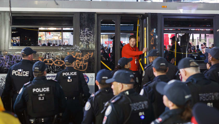 TORONTO, ON - JUNE 14: A man exits a smashed in bus in front of Toronto Police officers amidst celebrations on Yonge St. after the Toronto Raptors beat the Golden State Warriors in Game Six of the NBA Finals, on June 14, 2019 in Toronto, Canada. (Photo by Cole Burston/Getty Images)
