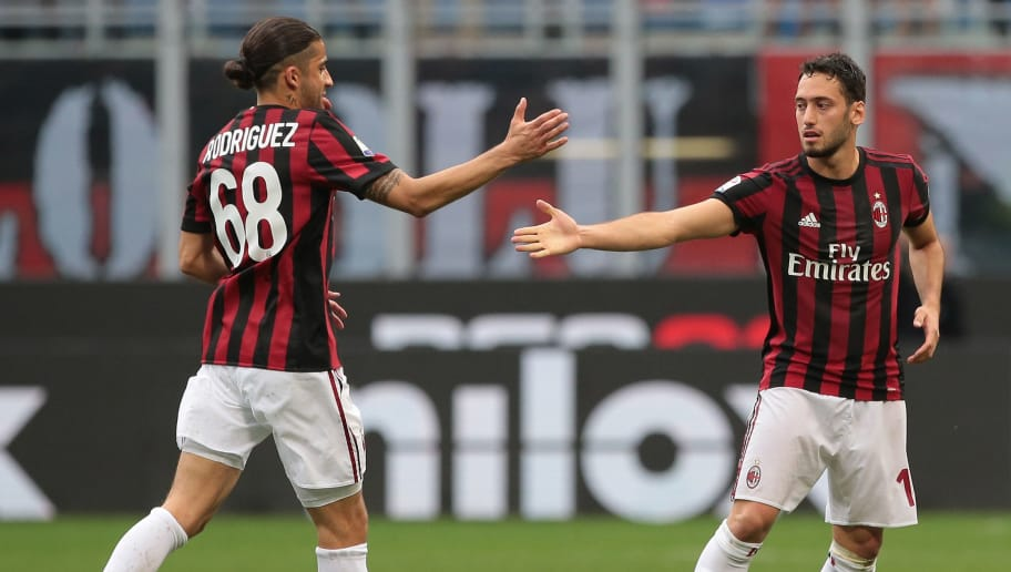 MILAN, ITALY - MAY 20:  Hakan Calhanoglu (R) of AC Milan celebrates his goal with his team-mate Ricardo Rodriguez during the serie A match between AC Milan and ACF Fiorentina at Stadio Giuseppe Meazza on May 20, 2018 in Milan, Italy.  (Photo by Emilio Andreoli/Getty Images)