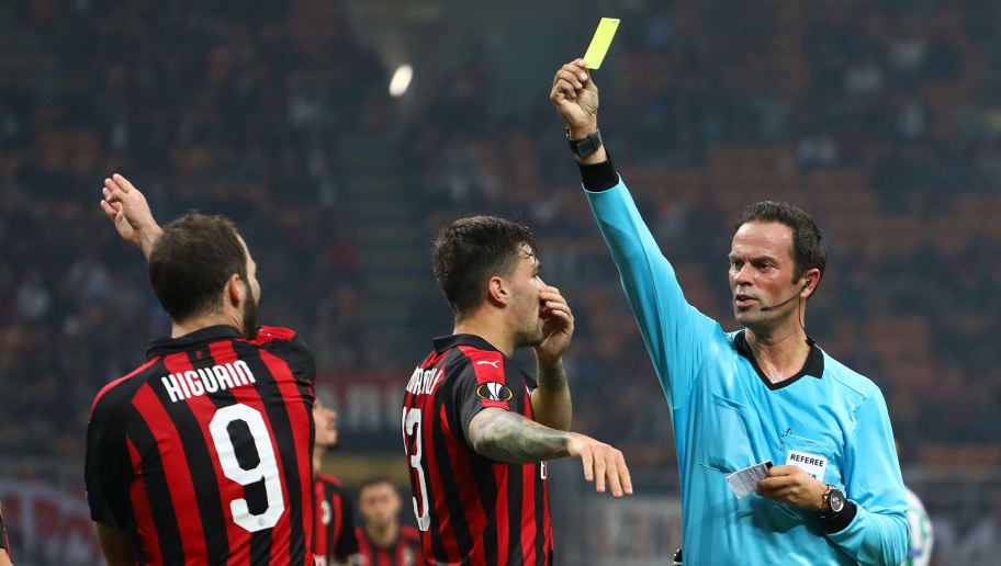 MILAN, ITALY - OCTOBER 25:  Referee Bas Nijhuis (R) shows the yellow card to Gonzalo Higuain #9 of AC Milan during the UEFA Europa League Group F match between AC Milan and Real Betis at Stadio Giuseppe Meazza on October 25, 2018 in Milan, Italy.  (Photo by Marco Luzzani/Getty Images)