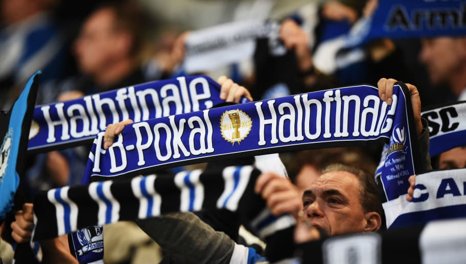 BIELEFELD, GERMANY - APRIL 29:  Fans of Bielefeld hold their semi final scarves during the DFB Cup semi final match between Arminia Bielefeld and VfL Wolfsburg at Schueco Arena on April 29, 2015 in Bielefeld, Germany.  (Photo by Stuart Franklin/Bongarts/Getty Images)