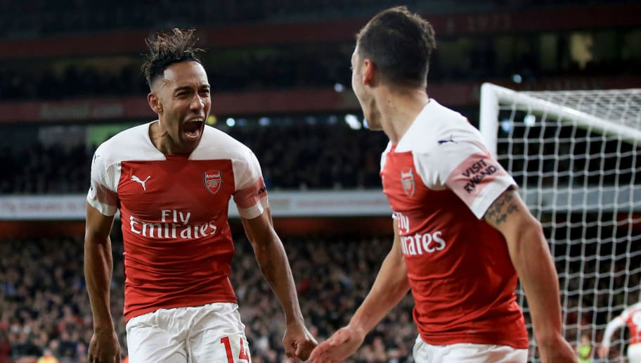 LONDON, ENGLAND - OCTOBER 22:  Pierre-Emerick Aubameyang of Arsenal celebrates scoring their 3rd goal with Mesut Ozil during the Premier League match between Arsenal FC and Leicester City at Emirates Stadium on October 22, 2018 in London, United Kingdom. (Photo by Marc Atkins/Getty Images)