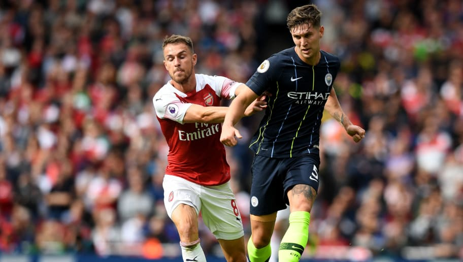 LONDON, ENGLAND - AUGUST 12:  John Stones of Manchester City passes the ball under pressure from Aaron Ramsey of Arsenal during the Premier League match between Arsenal FC and Manchester City at Emirates Stadium on August 12, 2018 in London, United Kingdom.  (Photo by Michael Regan/Getty Images)