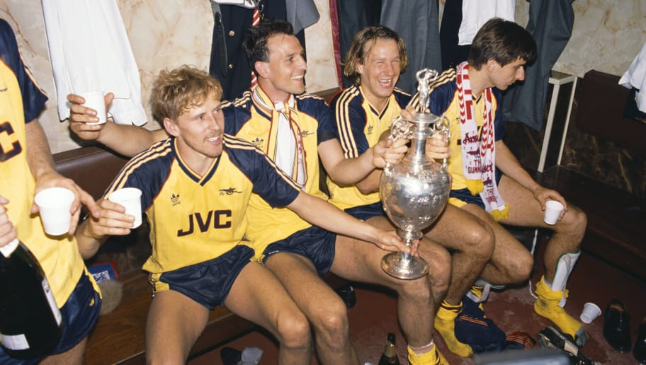 LIVERPOOL, UNITED KINGDOM - MAY 26:  Arsenal players from left Kevin Richardson, Steve Bould, Paul Merson and Alan Smith celebrate in the dressing room with the League Division One trophy after Arsenal had beaten Liverpool 2-0 in the final game of the season to pip Liverpool to the title, at Anfield on May 26, 1989 in Liverpool, England. (Photo by Allsport/Getty Images)