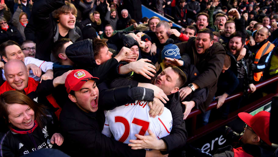 BIRMINGHAM, ENGLAND - FEBRUARY 14:  A Liverpool fan kisses Divock Origi of Liverpool as he celebrates after scoring his team's fourth goal during the Barclays Premier League match between Aston Villa and Liverpool at Villa Park on February 14, 2016 in Birmingham, England.  (Photo by Stu Forster/Getty Images)