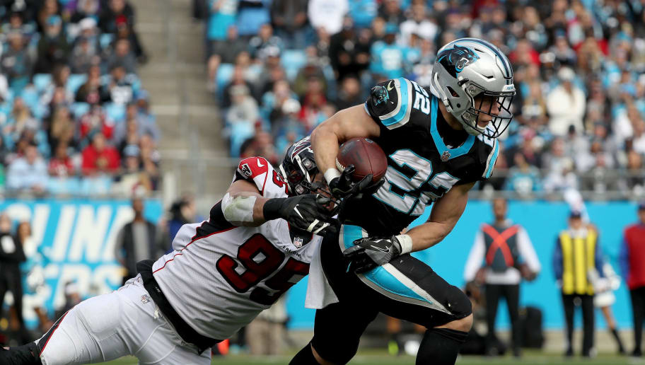CHARLOTTE, NORTH CAROLINA - DECEMBER 23: Christian McCaffrey #22 of the Carolina Panthers tries to break away from Jack Crawford #95 of the Atlanta Falcons during their game at Bank of America Stadium on December 23, 2018 in Charlotte, North Carolina. (Photo by Streeter Lecka/Getty Images)