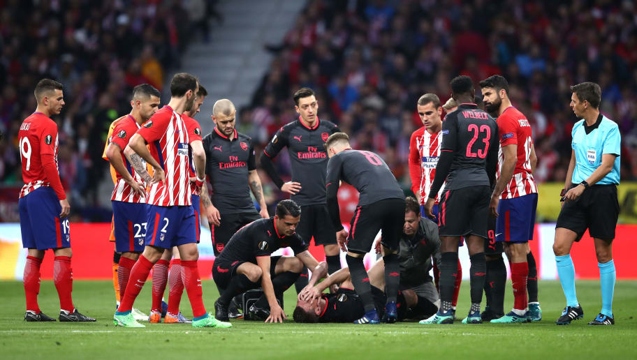 MADRID, SPAIN - MAY 03:  Laurent Koscielny of Arsenal lies injured during the UEFA Europa League Semi Final second leg match between Atletico Madrid  and Arsenal FC at Estadio Wanda Metropolitano on May 3, 2018 in Madrid, Spain.  (Photo by Lars Baron/Getty Images)