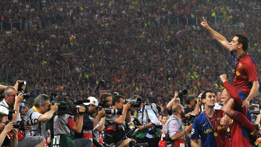 Barcelona's Xavi Hernandez (top) celebrates after winning the UEFA football Champions League final against Manchester United on May 27, 2009 at the Olympic Stadium in Rome. AFP PHOTO / CARL DE SOUZA (Photo credit should read CARL DE SOUZA/AFP/Getty Images)