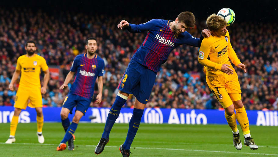 BARCELONA, SPAIN - MARCH 04: Gerard Pique of FC Barcelona competes for the ball with Antoine Griezmann of Club Atletico de Madrid during the La Liga match between Barcelona and Atletico Madrid at Camp Nou on March 4, 2018 in Barcelona, Spain.  (Photo by David Ramos/Getty Images)