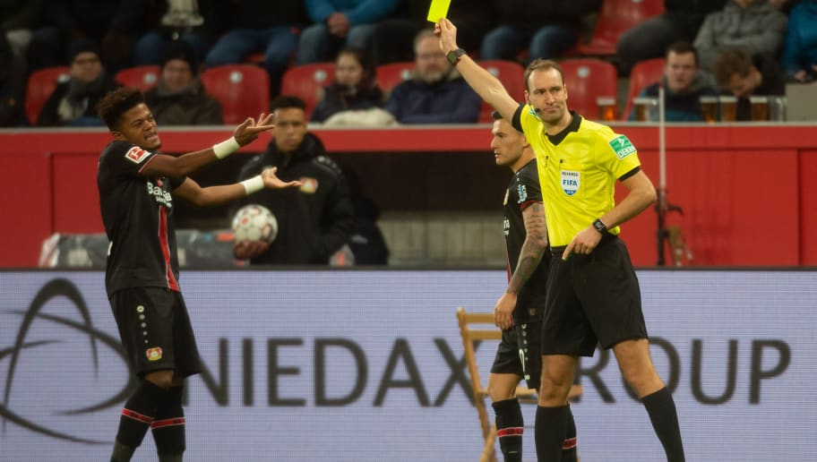 LEVERKUSEN, GERMANY - DECEMBER 08: Referee Bastian Dankert displays yellow card for Leon Bailey of Leverkusen during the Bundesliga match between Bayer 04 Leverkusen and FC Augsburg at BayArena on December 8, 2018 in Leverkusen, Germany. (Photo by Juergen Schwarz/Bongarts/Getty Images)
