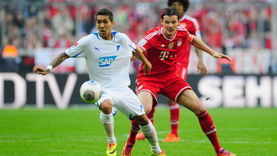MUNICH, GERMANY - MARCH 29:  Daniel van Buyten (R) of Muenchen challenges Roberto Firmino of Hoffenheim during the Bundesliga match between FC Bayern Muenchen and 1899 Hoffenheim at Allianz Arena on March 29, 2014 in Munich, Germany.  (Photo by Lennart Preiss/Bongarts/Getty Images)