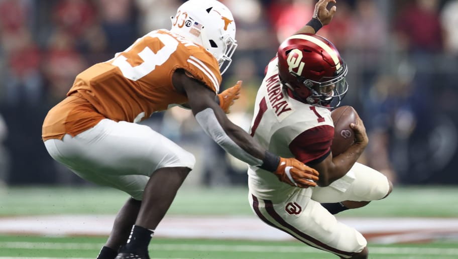 ARLINGTON, TEXAS - DECEMBER 01:  Kyler Murray #1 of the Oklahoma Sooners is tackled by Jerrod Heard #13 of the Texas Longhorns in the first quarter at AT&T Stadium on December 01, 2018 in Arlington, Texas. (Photo by Ronald Martinez/Getty Images)