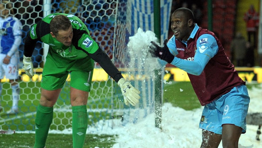 Blackburn's English goalkeeper Paul Robinson (L) plays in the snow with West Ham United's English striker Carlton Cole (R) during the English Premier League football match between Blackburn Rovers and West Ham United at Ewood Park in Blackburn, north-west England, on December 18, 2010. AFP PHOTO/ANDREW YATESFOR EDITORIAL USE ONLY Additional licence required for any commercial/promotional use or use on TV or internet (except identical online version of newspaper) of Premier League/Football League photos. Tel DataCo +44 207 2981656. Do not alter/modify photo. (Photo credit should read ANDREW YATES/AFP/Getty Images)