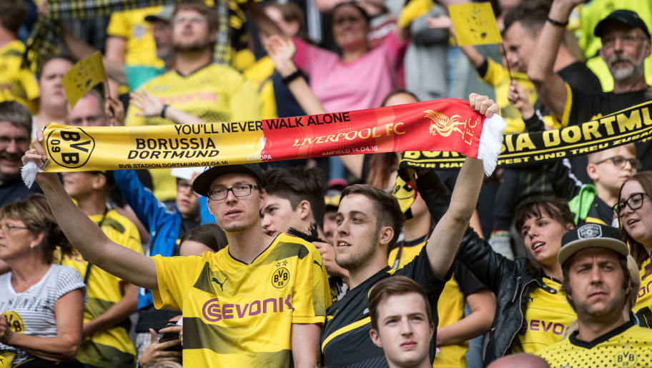 DORTMUND, GERMANY - AUGUST 11:  Supporters of Borussia Dortmunds wave a scarf with the Logo of both team before the friendly game Borussia Dortmund Legends - FC Liverpool Legends  during the session opening of the Borussia Dortmund on August 11, 2018 in Dortmund, Germany.  (Photo by Thomas Lohnes/Getty Images)