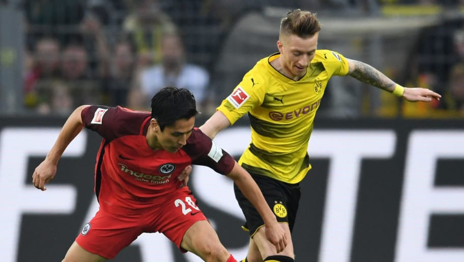 DORTMUND, GERMANY: Marco Reus of Borussia Dortmund and Makoto Hasebe of Eintrackt Frankfurt compete for the ball during the Bundesliga match between Borussia Dortmund and Eintracht Frankfurt at Signal Iduna Park on March 11, 2018 in Dortmund, Germany. (Photo by Etsuo Hara/Getty Images)