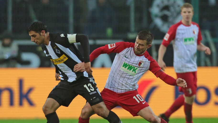 MOENCHENGLADBACH, GERMANY - JANUARY 20: Lars Stindl of Moenchengladbach and Daniel Baier of Augsburg battle for the ball during the Bundesliga match between Borussia Moenchengladbach and FC Augsburg at Borussia-Park on January 20, 2018 in Moenchengladbach, Germany. (Photo by TF-Images/TF-Images via Getty Images)