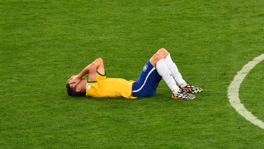 BELO HORIZONTE, BRAZIL - JULY 08:  A dejected Oscar of Brazil lies on the pitch after being defeated by Germany 7-1 during the 2014 FIFA World Cup Brazil Semi Final match between Brazil and Germany at Estadio Mineirao on July 8, 2014 in Belo Horizonte, Brazil.  (Photo by Jamie McDonald/Getty Images)