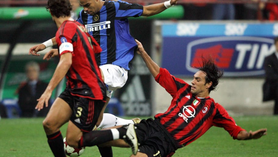 MILAN, ITALY:  Brazilian Adriano (C) of Inter-Milan is tackled by Alessandro Nesta (R) of AC Milan and his teammate Paolo Maldini during their Italian Serie A football match at Meazza stadium in Milan 24 October 2004.  AFP PHOTO/ Vincenzo PINTO  (Photo credit should read VINCENZO PINTO/AFP/Getty Images)