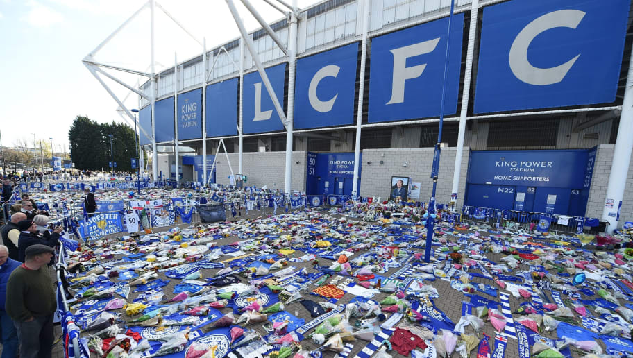 People pause at the tributes gathered outside Leicester City Football Club's King Power Stadium in Leicester, eastern England, on October 31, 2018 in honour and remembrance of those who died in a helicopter crash at the club's stadium on October 27 including the club's Thai chairman Vichai Srivaddhanaprabha. - Leicester City's chairman Vichai Srivaddhanaprabha was among five people killed when his helicopter crashed and burst into flames in the Premier League side's stadium car park moments after taking off from the pitch, the club said on October 28. A stream of fans already fearing the worst had laid out flowers, football scarves and Buddhist prayers outside the club's King Power stadium after Saturday's accident in tribute to the Thai billionaire boss -- the man they credit for an against-all-odds Premier League victory in 2016 (Photo by Paul ELLIS / AFP)        (Photo credit should read PAUL ELLIS/AFP/Getty Images)