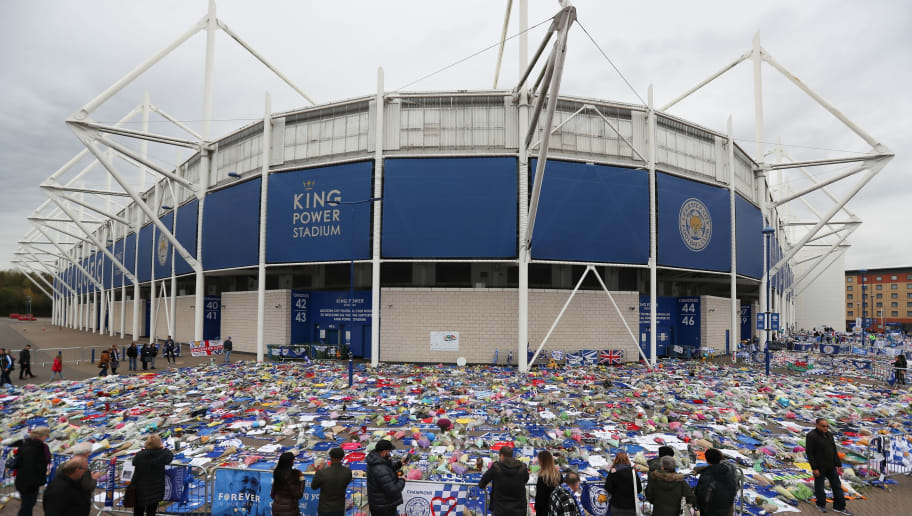 People pause to view and pay their respects at the tributes layed outside Leicester City Football Club's King Power Stadium in Leicester, eastern England, on November 1, 2018 after the helicopter of the club's Thai chairman Vichai Srivaddhanaprabha went down on October 27 killing five passengers including the chairman. - Leicester City's chairman Vichai Srivaddhanaprabha was among five people killed when his helicopter crashed and burst into flames in the Premier League side's stadium car park moments after taking off from the pitch, the club said on October 28. A stream of fans already fearing the worst had laid out flowers, football scarves and Buddhist prayers outside the club's King Power stadium after Saturday's accident in tribute to the Thai billionaire boss -- the man they credit for an against-all-odds Premier League victory in 2016 (Photo by Daniel LEAL-OLIVAS / AFP)        (Photo credit should read DANIEL LEAL-OLIVAS/AFP/Getty Images)