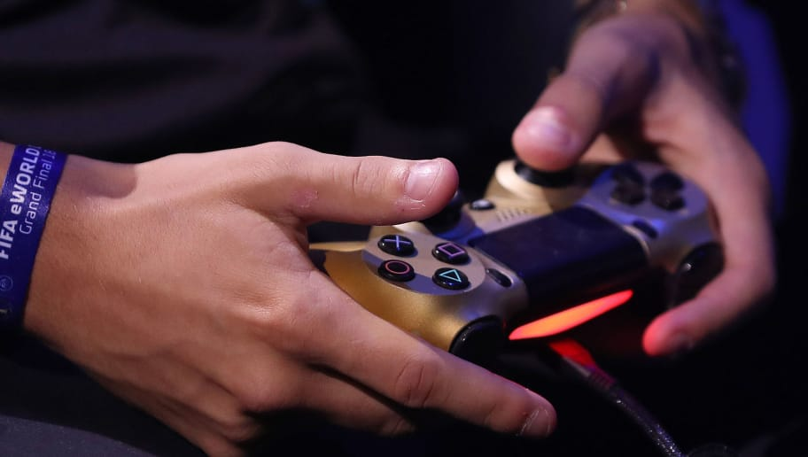 A players uses a games controller as he competes in the group stages of the FIFA eWorld Cup Grand Final, at the O2 in London on August 2, 2018. - The FIFA eWorld Cup Grand Final 2018 will see 32 finalists battle it out for the main prize  the title of FIFA eWorld Cup champion, and pocket USD 250,000 in prize money. (Photo by Daniel LEAL-OLIVAS / AFP)        (Photo credit should read DANIEL LEAL-OLIVAS/AFP/Getty Images)