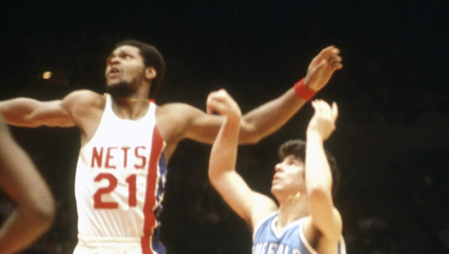 UNIONDALE, NY - CIRCA 1977:  Ernie DiGregorio #15 of the Buffalo Braves shoots over Tim Bassett #21 of the New Jersey Nets during an NBA basketball game circa 1977 at the Nassau Veterans Memorial Coliseum in Uniondale, New York. DiGregorio played for the Braves from 1973-77. (Photo by Focus on Sport/Getty Images)