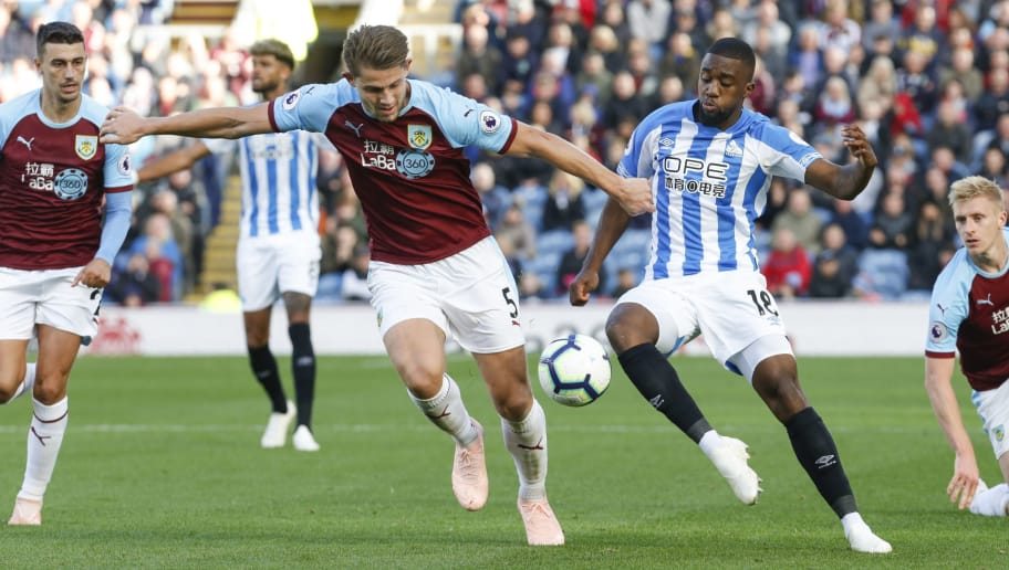 BURNLEY, ENGLAND - OCTOBER 06: Isaac Mbenza of Huddersfield Town is tackled by James Tarkowski of Burnley during the Premier League match between Burnley FC and Huddersfield Town at Turf Moor on October 6, 2018 in Burnley, United Kingdom. (Photo by John Early/Getty Images)