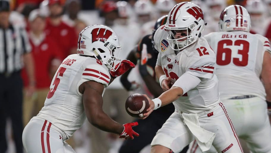 MIAMI GARDENS, FL - DECEMBER 30: Alex Hornibrook #12 hands the ball off to Chris James #5 of the Wisconsin Badgers against the Miami Hurricanes during the 2017 Capital One Orange Bowl at Hard Rock Stadium on December 30, 2017 in Miami Gardens, Florida. Wisconsin defeated Miami 34-24. (Photo by Joel Auerbach/Getty Images)
