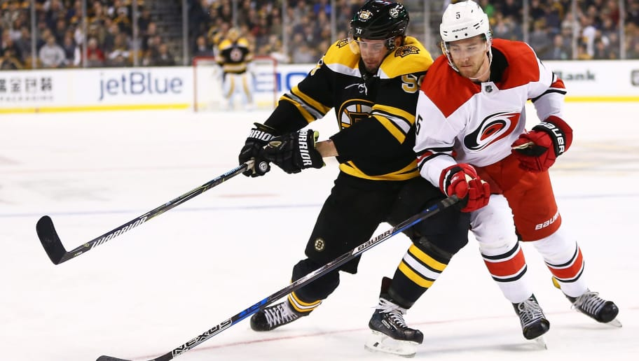 BOSTON, MA - FEBRUARY 27: Tim Schaller #59 of the Boston Bruins and Noah Hanifin #5 of the Carolina Hurricanes fight for the puck in the third period of a game at TD Garden on February 27, 2018 in Boston, Massachusetts. NOTE TO USER: User expressly acknowledges and agrees that, by downloading and or using this photograph, User is consenting to the terms and conditions of the Getty Images License Agreement. (Photo by Adam Glanzman/Getty Images)