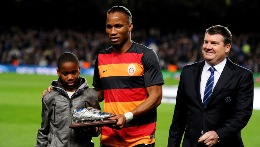 LONDON, ENGLAND - MARCH 18:  Former Chelsea player Didier Drogba of Galatasaray and son Isaac on the pitch with Ron Gourlay, Chief Executive of Chelsea prior to the UEFA Champions League Round of 16 second leg match between Chelsea and Galatasaray AS at Stamford Bridge on March 18, 2014 in London, England.  (Photo by Mike Hewitt/Getty Images)