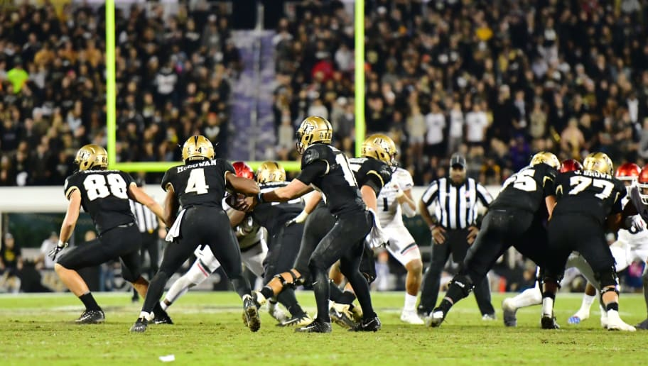 ORLANDO, FLORIDA - NOVEMBER 17: McKenzie Milton #10 hands the ball off to Taj McGowan #4 of the UCF Knights during the fourth quarter against the Cincinnati Bearcats on November 17, 2018 at Spectrum Stadium in Orlando, Florida. (Photo by Julio Aguilar/Getty Images)