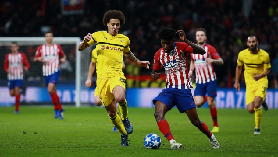 MADRID, SPAIN - NOVEMBER 06: Thomas Teye Partey (R) of Atletico de Madrid competes for the ball with Axel Witsel of Borussia Dortmund during the Group A match of the UEFA Champions League between Club Atletico de Madrid and Borussia Dortmund at Estadio Wanda Metropolitano on November 06, 2018 in Madrid, Spain. (Photo by Gonzalo Arroyo Moreno/Getty Images)