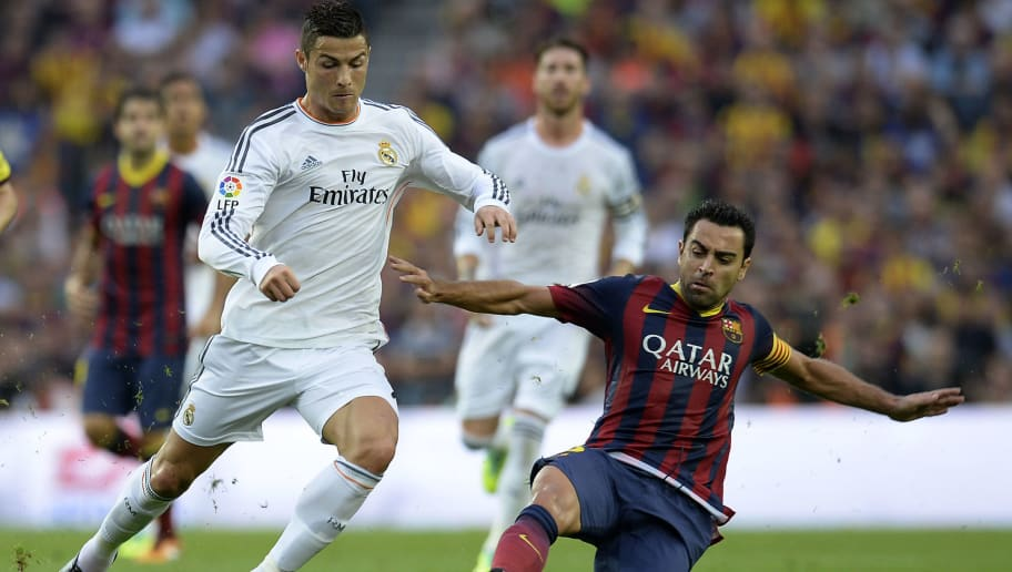 Real Madrid's Portuguese forward Cristiano Ronaldo (L) vies with Barcelona's midfielder Xavi Hernandez during the Spanish league Clasico football match FC Barcelona vs Real Madrid CF at the Camp Nou stadium in Barcelona on October 26, 2013.   AFP PHOTO/ LLUIS GENE        (Photo credit should read LLUIS GENE/AFP/Getty Images)