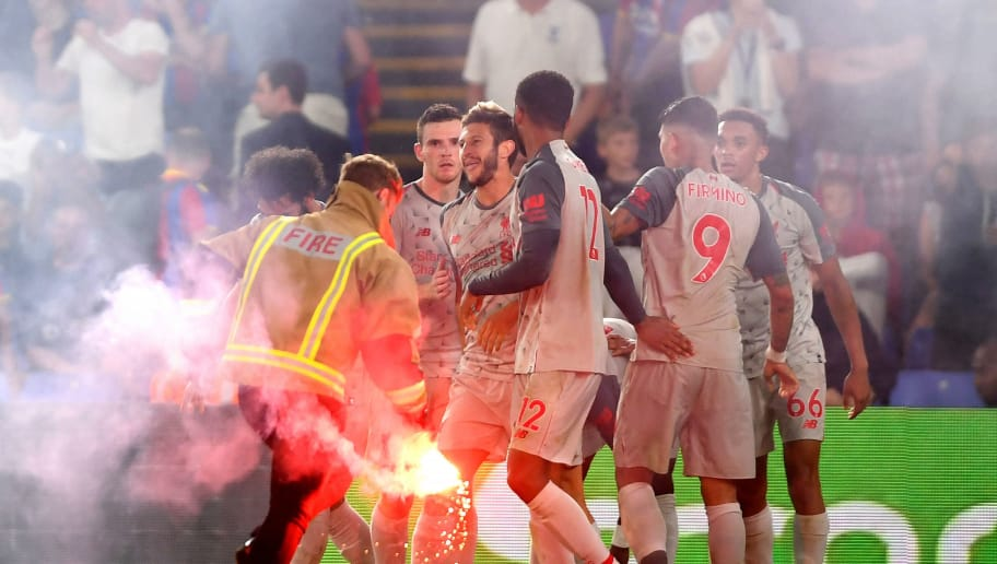 LONDON, ENGLAND - AUGUST 20:  A flare is removed from the pitch, following Sadio Mane of Liverpool celebrating scoring his team's second goal with team mates during the Premier League match between Crystal Palace and Liverpool FC at Selhurst Park on August 20, 2018 in London, United Kingdom.  (Photo by Mike Hewitt/Getty Images)